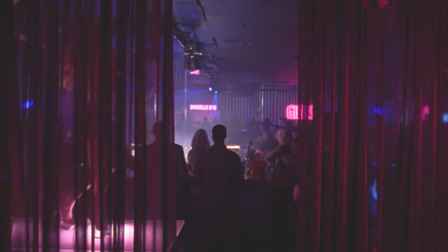 vidéos et rushes de medium angle of bar at strip club or nightclub crowded with people. women pole dancing. adult entertainment. - peep show