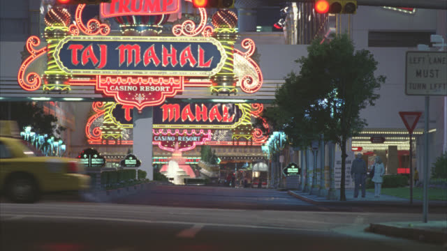 medium angle of entrance to taj mahal hotel and casino. neon lights and signs. gambling. mini cooper car driving in then backing up in reverse. - atlantic city stock videos & royalty-free footage