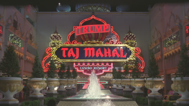 medium angle of entrance and neon sign for trump taj mahal upper class hotel and casino. arabian, islamic or indian themed. gambling. courtyard and fountain. - casino stock videos & royalty-free footage