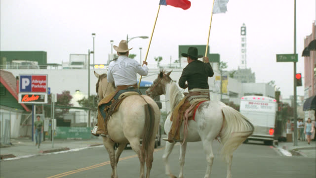 medium angle of greyhound buses pulling into and out of houston bus terminal or bus station. two cowboys on horseback hold texas state flag and flag for houston livestock show and rodeo. - texas stock videos & royalty-free footage