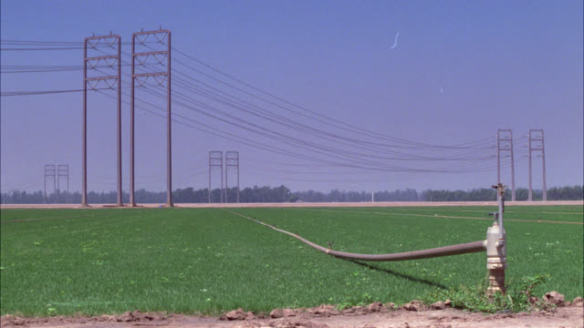 stockvideo's en b-roll-footage met wide angle of field or farmland near electrical or power wires. hose visible in fg. greyhound bus moves from right to left on road in bg. could be country. series. - commercieel landvoertuig