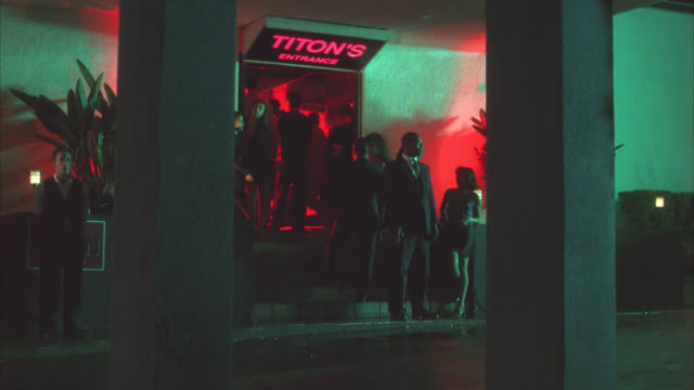 medium angle of people standing outside of entrance to nightclub, dance club or bar. sign reads titon's entrance. valet and bouncer. - 1998 stock videos & royalty-free footage