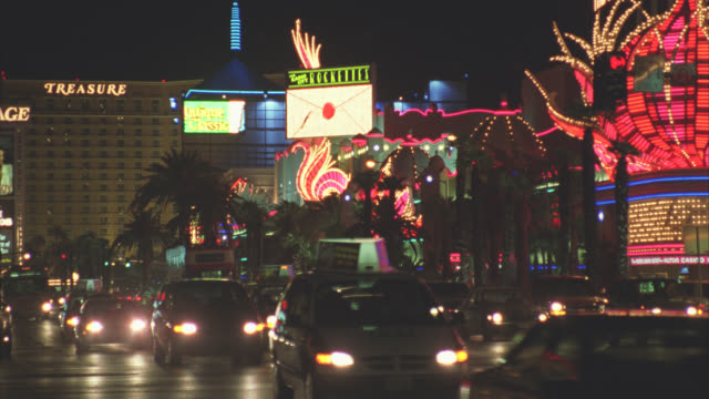 wide angle of cars and double-decker bus driving down las vegas strip or city street. flamingo hotel. neon lights and signs. gambling. - the strip las vegas stock videos & royalty-free footage