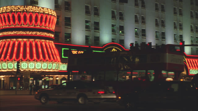 wide angle of cars and double-decker bus driving down las vegas strip or city street. flamingo hotel. neon lights and signs. gambling. - double decker bus stock videos & royalty-free footage