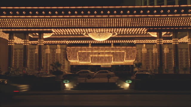 stockvideo's en b-roll-footage met wide angle of entrance to hotel or casino with lots of lights and chandeliers. cars and double-decker bus drive by.  could be aladdin hotel. - commercieel landvoertuig