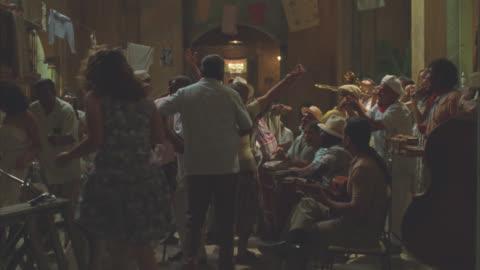 vídeos y material grabado en eventos de stock de pull back from townspeople dancing in town, streets, alley or patio. party or celebration. musicians. - villa asentamiento humano