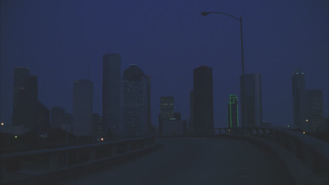 wide angle of houston city skyline. skyscrapers and high rise office or apartment buildings. freeway or highway off-ramp. convertible car or volkswagen beetle driving. - volkswagen stock-videos und b-roll-filmmaterial