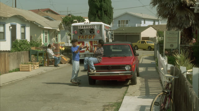 wide angle of two boys or children playing in street in middle class residential area or neighborhood. suburbs. man fanning himself with hat in bg. taco truck in bg. - テキサス州点の映像素材/bロール