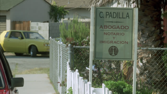 medium angle of sign in spanish for c. padilla abogado, notario y imigracion. lawyer, notary and immigration. law office. residential area or neighborhood. - テキサス州点の映像素材/bロール