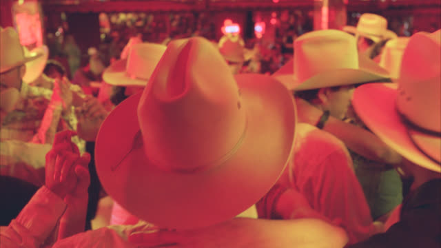 pull back from people, many wearing cowboy hats, dancing in bar, nightclub or dance club. country western. - cappello video stock e b–roll