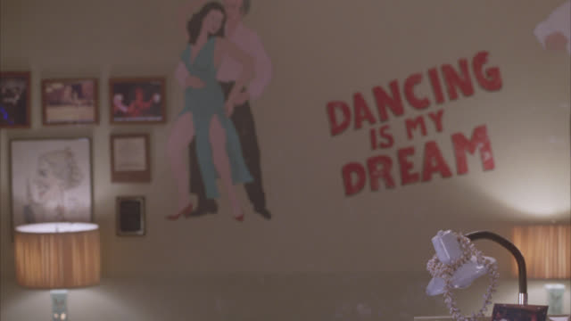 vidéos et rushes de medium angle of sign reading dancing is my dream with painting of two people ballroom dancing. pictures and awards or plaques on wall. - studio de danse