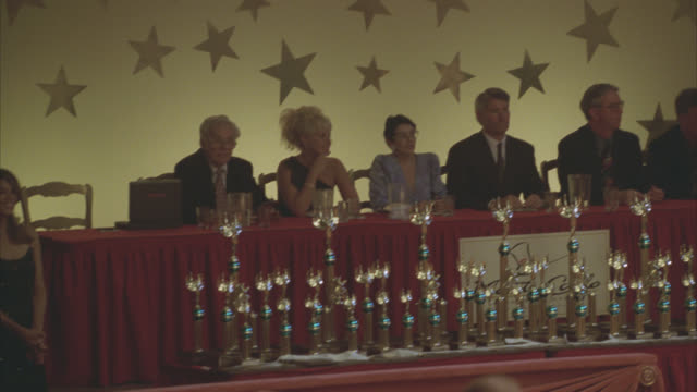 pan right to left of panel of judges sitting at table behind rows of trophies or awards. could be at contest or competition. stars hanging on wall in bg. - giudice video stock e b–roll