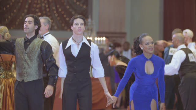 medium angle of couples, men and women, dancing in professional ballroom dance competition. dancers bow, hug and walk off-stage. audience or people watching in bg. - bowing stock videos & royalty-free footage