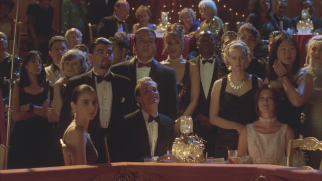 medium angle of people in audience. formal, black tie attire. could be in theater, benefit or reception. - formal reception stock videos and b-roll footage