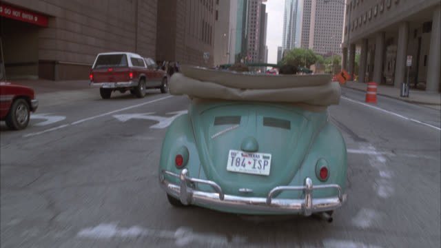 pan up driving pov following car, could be convertible volkswagen beetle, to skyscrapers or high rise office buildings. downtown city streets. - volkswagen stock-videos und b-roll-filmmaterial