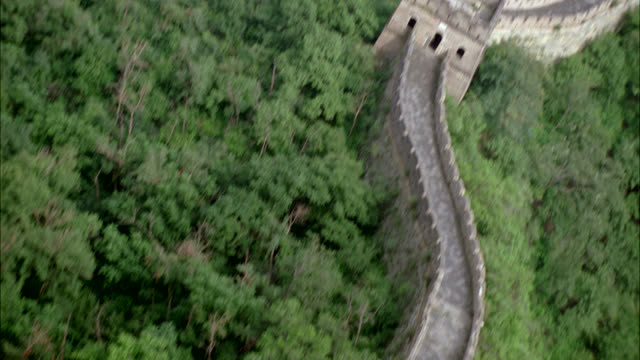 aerial over great wall of china in mountains. trees in forest. brick or stone wall with crenellation. landmarks. - great wall of china stock videos & royalty-free footage