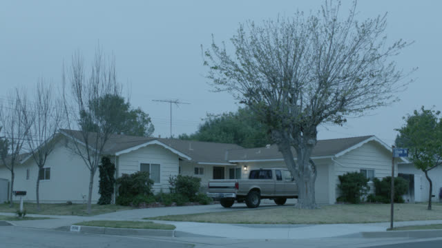 vidéos et rushes de wide angle of one story lower to middle class house with ford pickup truck in driveway. street corner. bare branches on trees. grass lawn. suburban. car. - bare tree