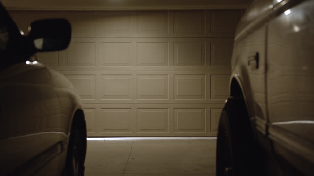medium angle pov from between two cars in driveway of garage door. light goes off in garage. - driveway stock videos & royalty-free footage