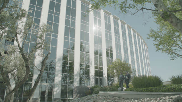 wide angle of two men in business suits walking left to right on sidewalk in courtyard area. trees and bushes visible. multi-story office building in fg. - courtyard stock videos & royalty-free footage