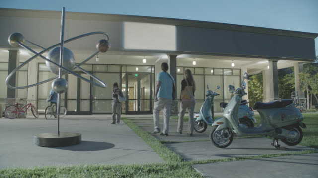 wide angle of yard or courtyard outside building. could be college campus or university. orbiting planet sculpture visible in yard. art. people stand near scooters or vespas. another person talks on phone. trees visible in bg. bikes parked outside buildin - push scooter stock videos & royalty-free footage