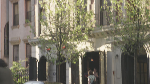 pan up from city street and pedestrians on sidewalk to multi-story brick apartment building. café visible in bottom of apartment building.  balconies and fire escapes visible. church with steeple visible next to apartment building. series. - steeple stock videos & royalty-free footage