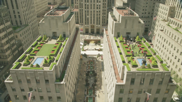 high angle down of rockefeller center. buildings and rooftops visible. pedestrians visible on  walk way below. fountains visible. gardens visible on rooftops. one roof set up for party or event. statue or sculpture visible in square below. rockefeller pla - städtischer platz stock-videos und b-roll-filmmaterial