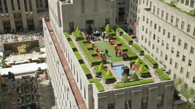 high angle down pan right to left of rockefeller center. buildings and rooftops visible. pedestrians visible on  walk way below. fountains visible. gardens visible on rooftops. one roof set up for party or event. statue or sculpture visible in square belo - rockefeller center video stock e b–roll