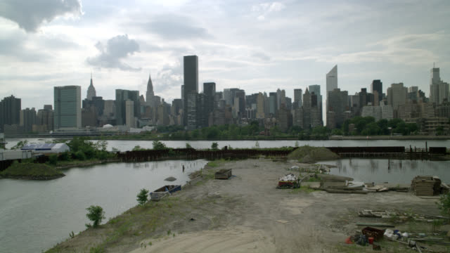 stockvideo's en b-roll-footage met high angle down of ship yard, industrial area, or storage yard area outside city. city skyline visible across rivers or bay. trees visible in bg. rubbage, garbage containers, trash, and building or construction suppilies visible in warehouse yard. sand or - metlife building