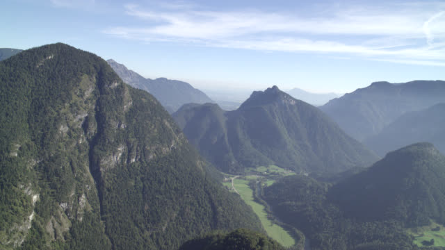 stockvideo's en b-roll-footage met aerial of bavarian alps. forests and trees visible on mountains. blue skies and clouds. winding mountain road partially visible. - beieren