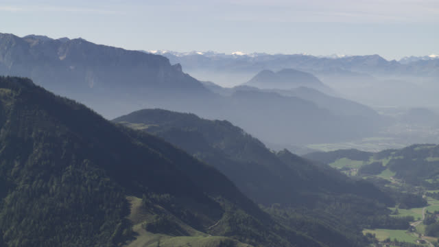 stockvideo's en b-roll-footage met aerial of mountains with trees and forests in bavaria. valleys with small towns or villages visible. snow capped mountains in bg. could be alps. - beieren