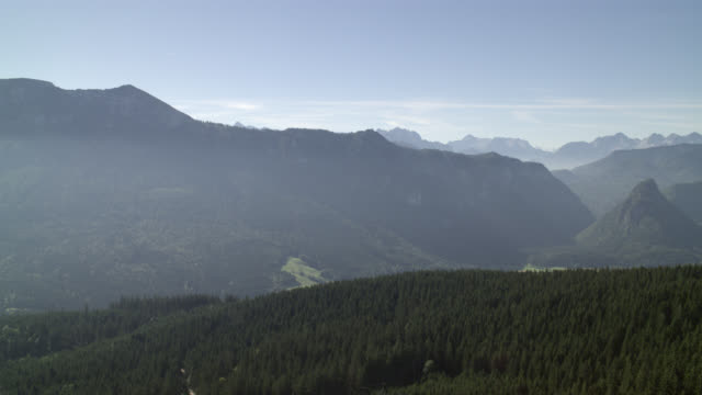 aerial of mountains, valleys, and forests in riederstein bavaria. winding mountain road visible. small town or village visible. rural areas and countrysides. blue skies and clouds. - valley stock videos & royalty-free footage