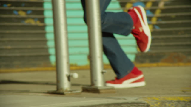 MEDIUM ANGLE OF PERSON WITH JEANS AND RED SNEAKERS RUNNING ON SIDEWALK IN URBAN AREA FROM LEFT TO RIGHT. BRICK WALL AND STEPS, METAL GARAGE DOORS, BICYCLE, AND CEMENT VISIBLE.