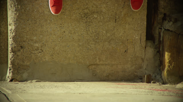 medium angle of person with jeans and red sneakers jumping down from concrete wall. could be loading zone. urban area. - anno 1970 video stock e b–roll