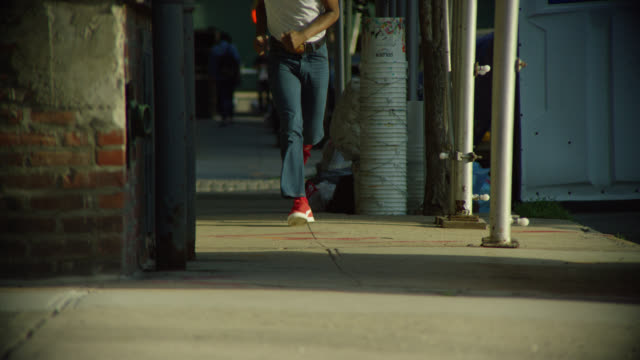 medium angle of male teenager in white tank top, jeans, and red sneakers running or jogging on sidewalk from bg to fg. urban area. other pedestrians visible. - 1970 stock videos & royalty-free footage