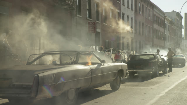 vídeos de stock, filmes e b-roll de medium angle of two cars burning on fire on city street in lower class urban area. smoke rises into air. pedestrians visible. brick apartment buildings visible in bg. - bronx new york