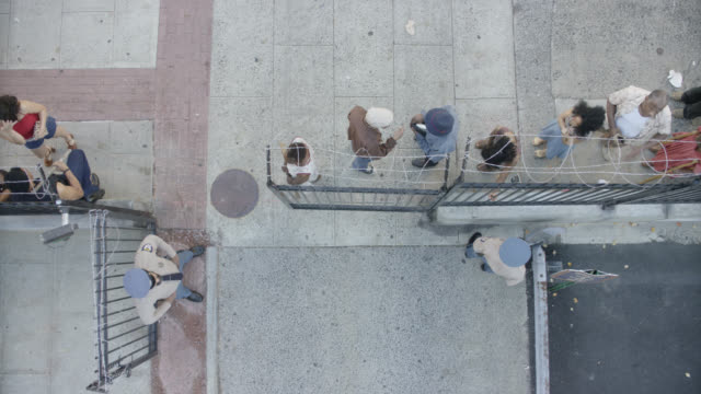 high angle down of people waiting in line near fence with barbed wire and uniformed guards. could be homeless shelter, jail, or prison. city street. - wachmann stock-videos und b-roll-filmmaterial
