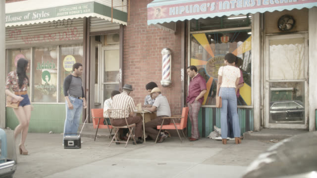 medium angle moving pov from right to left of men playing cards outside of barber shop in urban area.  man visible dancing next to radio as pedestrians walk down sidewalk. cars partially visible parked on street. could be neighborhood. - barber stock videos & royalty-free footage