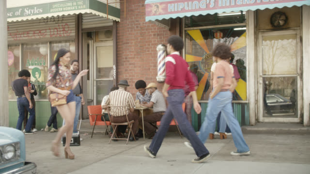 vídeos de stock e filmes b-roll de medium angle moving pov from right to left of men playing cards outside of barber shop in urban area.  man visible dancing next to radio as pedestrians walk down sidewalk. cars partially visible parked on street. could be neighborhood. - rádio