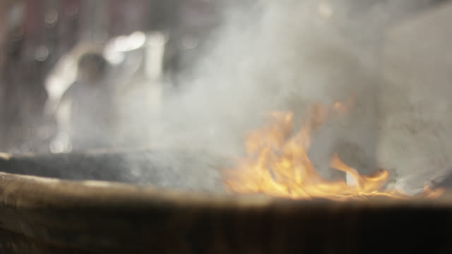 close angle of fire or flames. could be barrel or trash can. could be grill. smoke rises. - dustbin stock videos & royalty-free footage