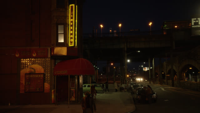 "medium angle of entrance to ""inferno"" nightclub on street corner of lower class urban area. neon sign illuminated. awning over entrance. people visible on street corner. overpass or bridge visible. - eastern usa stock videos and b-roll footage"