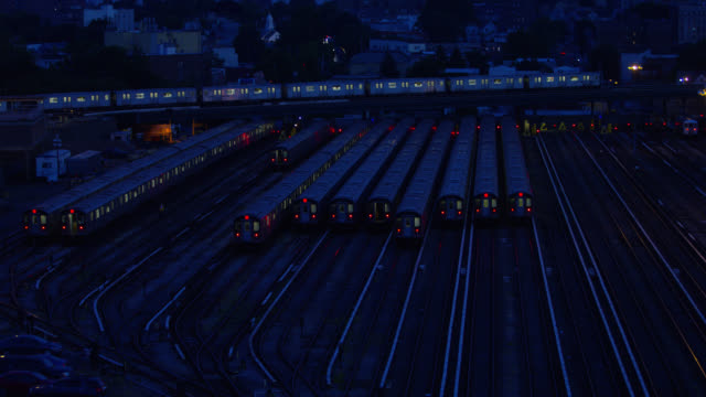wide angle of railroad tracks in train depot or rail yard. train visible moving on tracks from right to left. other train cars sitting on tracks. houses, city skyline, or apartment buildings visible in bg. cars visible driving on city street. - 操車場点の映像素材/bロール