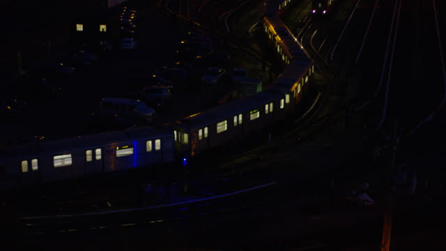 pan up of railroad yard or train depot. train cars visible parked on railroad tracks. another train moves from bg to fg. - 操車場点の映像素材/bロール
