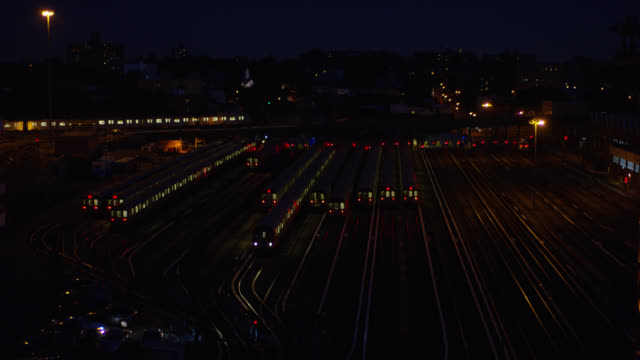 wide angle of train moving through railroad yard or train depot from left to right. other train cars parked on railroad tracks. - 操車場点の映像素材/bロール