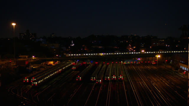wide angle of train cars parked on railroad tracks in railroad yard or train depot. train moves by from left to right in bg. - 操車場点の映像素材/bロール