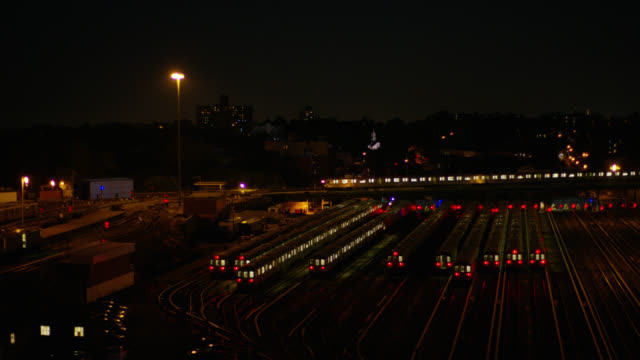 medium angle of train cars and trains parked on railroad tracks in railroad yard or train depot. train in bg moves on tracks from right to left. - 操車場点の映像素材/bロール