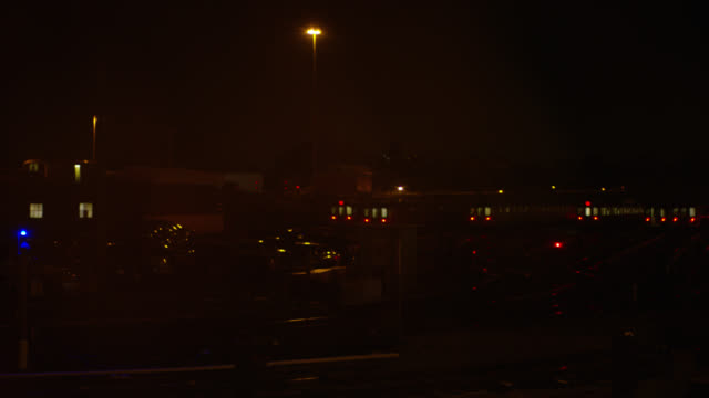 pan left to right of cars in parking lot and warehouse building to railroad tracks in railroad yard or train depot. train cars visible parked on tracks. - 操車場点の映像素材/bロール