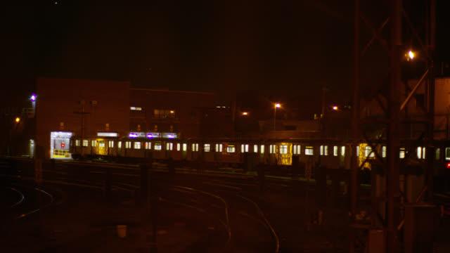 medium angle of train parked on railroad tracks outside of garage or warehouse in railroad yard or train depot. - 操車場点の映像素材/bロール