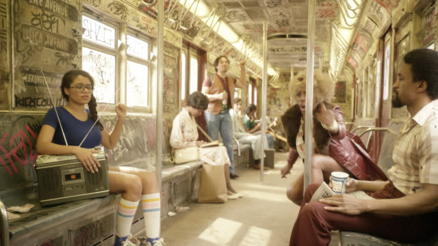 pull back on interior of subway train cars. passengers or commuters listen to radio. graffiti covers interior of train. woman stands up and dances while others dance in their seats. - dancing back to back stock videos & royalty-free footage