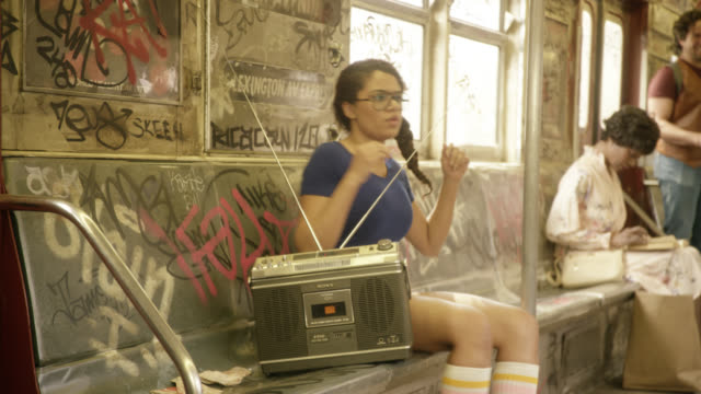 medium angle of interior of subway train cars. passengers or commuters listening to radio. graffiti covers interior of train. woman dances in her seat. - anno 1970 video stock e b–roll
