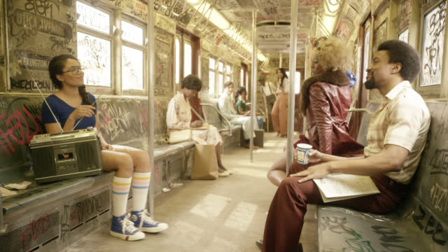 wide angle of interior of subway train cars. passengers or commuters listening to radio and dancing in seats. graffiti covers train car. woman stands to dance in aisle. - anno 1970 video stock e b–roll
